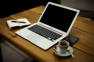 Mesa con ordenador, taza de café y libreta